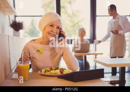 Pleasant conversation. Charming elderly woman having a conversation on the phone with her friend while eating salad in cafe and reading from her table - Stock Photo