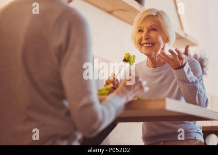 Happy senior woman sharing stories with her friend in cafe - Stock Photo