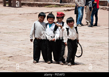 Young boys gather round to pose for a photograph in exchange for candy and sweets in the village at Taquile island, Lake Titicaca. Peru - Stock Photo