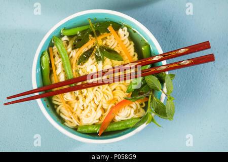 Nudelsuppe mit Mie-Nudeln, Karotten, grüne Bohnen, Paprika, Minze und Chili, Studio - Stock Photo