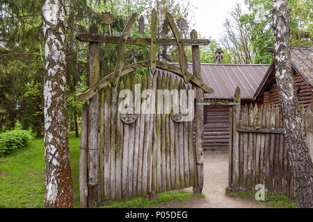 Old wooden gate with green moss and carved overlays in the form of the sun - Stock Photo