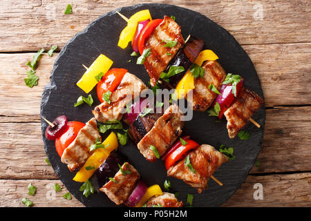 Juicy grilled kebabs of pork with tomatoes, pepper, onions and eggplants close-up on a slate plate on a table. horizontal top view from above - Stock Photo