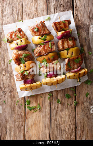 Rustic juicy kebabs of pork with apples and red onions close-up on parchment on the table. Vertical top view from above - Stock Photo