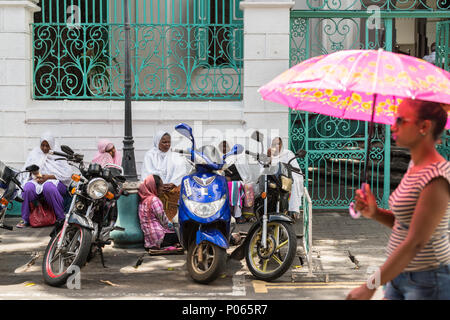 A young woman walking past a group of women sitting on the street waiting for alms outside Jummah Mosque on a Friday, Port Louis,  Mauritius - Stock Photo