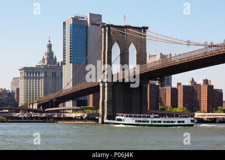 Tourist boat going under Brooklyn Bridge, East River, Brooklyn, New York City, USA - Stock Photo