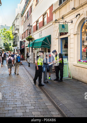 Gibraltar, UK - May 18, 2017: Police Officers gives direction advice to tourists at Main Street of Gibraltar, United Kingdom, Western Europe. - Stock Photo