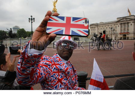 London, UK, 9 June 2018. The annual Trooping the Colour has taken place in London in honour of Queen Elizabeth's birthday. Thousands lined the streets to welcome Her Majesty and other members of the Royal Family as they travelled by coach from Buckingham Palace to Horse Guards Parade. Here there's time for a selfie before the parade as Joseph Afrane waits for the parade to begin. Credit: Clearpix/Alamy Live News - Stock Photo
