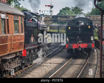 J27 Locomotive 65894 (NER P3 2392) and LNER B1 4-6-0 locomotive 1264 (BR 6124) approaching Goathland station on North York Moors Railway - Stock Photo