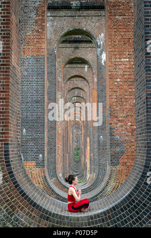 woman sitting in the arches of the Ouse Valley Viaduct practicing yoga and meditating - Stock Photo