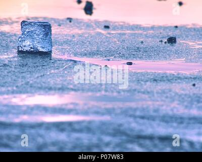 Blue and white pieces of broken ice. Melting of  broken ice pieces, crushed floes on frozen lake. Warm colors of evening sun in reflections. - Stock Photo