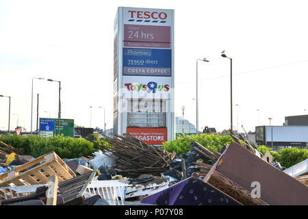 Fly tipping rubbish is left in front of the shop signs including Tesco Direct and The Toys R Us both now closed stores, on the North Circular, near th - Stock Photo
