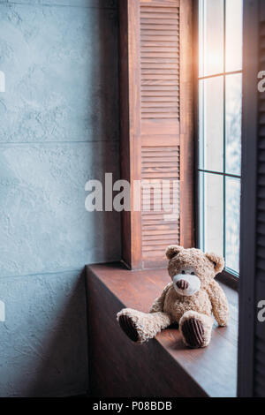 teddy bear on windowsill of stylish room in loft style - Stock Photo