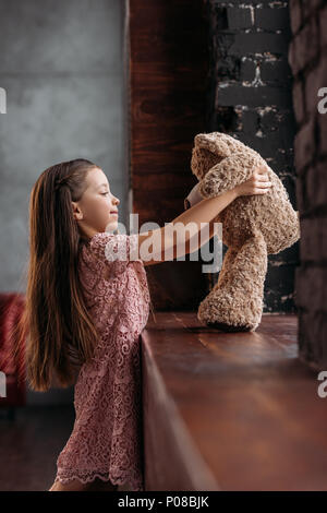 adorable little child playing with teddy bear on windowsill - Stock Photo