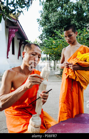 Luang Prabang, Laos, Southeast Asia : A Buddhist monk carves a wooden Buddha statuette as a younger novice looks at, at a monastery in Luang Prabang. - Stock Photo