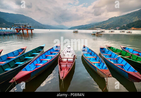 Color boats at Phewa lake shore in Pokhara, Nepal. - Stock Photo