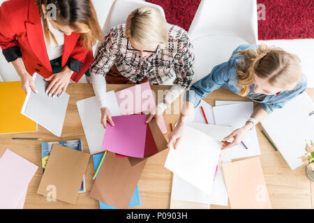 overhead view of fashionable magazine editors working with color palette in modern office - Stock Photo
