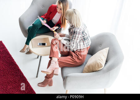 overhead view of fashionable magazine editors working in modern office - Stock Photo