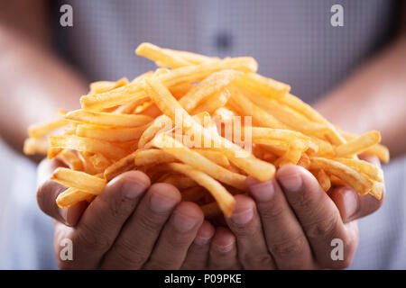 closeup of a young caucasian man with a bunch of appetizing french fries in his hands - Stock Photo