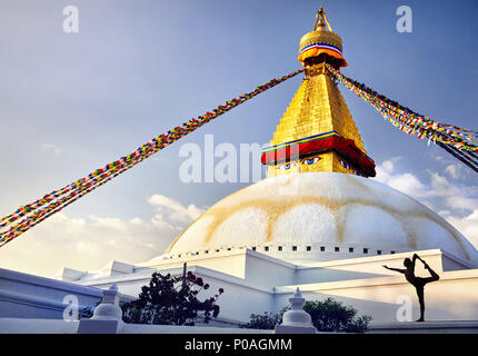 Silhouette of man doing yoga natarajasana at Bodnath Great Buddhist Stupa with prayer flags in Kathmandu - Stock Photo