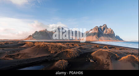 Evening atmosphere at the long lava beach, black sandy beach, dunes covered with dry grass, mountains Klifatindur - Stock Photo