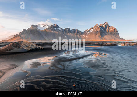 Evening atmosphere at the lava beach, black sandy beach, mountains Klifatindur, Eystrahorn and Kambhorn, headland Stokksnes - Stock Photo