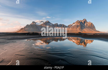 Evening atmosphere at the long lava beach, black sand beach, reflection in the water, mountains Klifatindur - Stock Photo