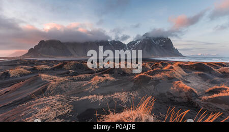 Evening atmosphere at the lava beach, black sandy beach with dunes, overgrown with dry grass, mountains Klifatindur - Stock Photo