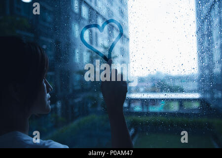 sad lonely love woman in rain draw heart on windows glass dark blue tone - Stock Photo