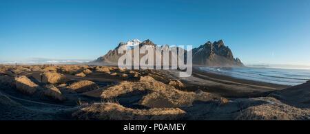 Lava beach, black sand beach, overgrown dunes, mountains Klifatindur, Eystrahorn and Kambhorn, headland Stokksnes - Stock Photo