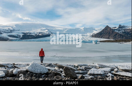 Man stands at Frozen Lagoon with ice floe, mountains, Fjallsárlón Glacier Lagoon, South Iceland, Iceland - Stock Photo