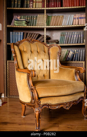 Books on bookshelves. Luxury yellow armchair in library room.Still Life of Vintage Chair.Old vintage furniture,beige armchair - Stock Photo