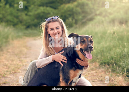 Happy smiling black dog wearing a walking harness sitting facing its pretty young woman owner who is caressing it with a loving smile outdoors in coun - Stock Photo