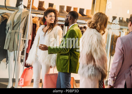 cropped shot of young stylish couples shopping in mall - Stock Photo