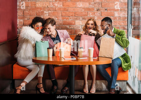 smiling trendy multiethnic young people looking into paper bags while drinking coffee together - Stock Photo