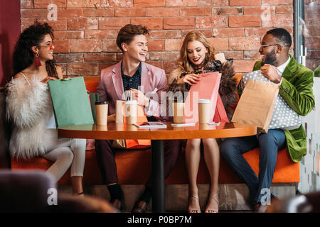 fashionable multiethnic young people looking into paper bags while drinking coffee together - Stock Photo