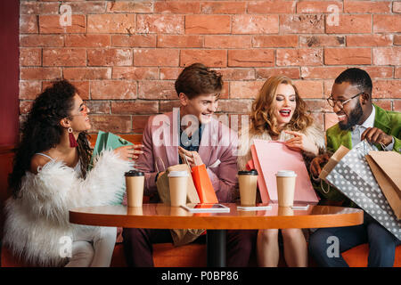 stylish multiethnic young people looking into shopping bags while drinking coffee together - Stock Photo