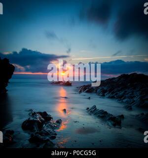 Cloudy sunset over the rocks along the Cornish coast near Newquay, Cornwall, England - Stock Photo