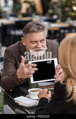 senior businessman with tablet having business meeting with colleague in cafe - Stock Photo