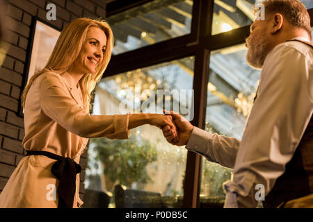 side view of business colleagues shaking hands after meeting in cafe - Stock Photo
