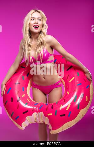 Cheerful blonde woman in bikini wearing swimming tube in shape of doughnut and looking away - Stock Photo