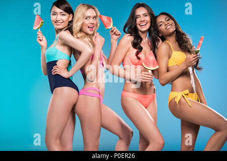 attractive women in swimsuits smiling and posing with watermelon pieces - Stock Photo