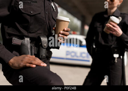 cropped shot of police officers having coffee break - Stock Photo