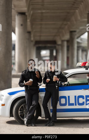 police officers with coffee and doughnuts standing next to car - Stock Photo