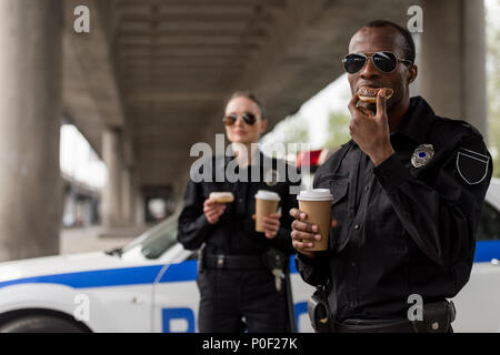 young police officers having coffee break with doughnuts in front of police car - Stock Photo