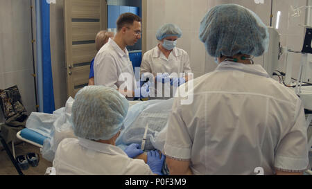 Doctors performing endoscopic procedure in hospital - Stock Photo