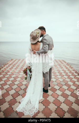 back view of bride and groom in boho style hugging and kissing on pier at lake - Stock Photo