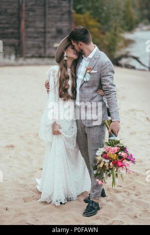 beautiful bride and groom in boho style kissing on beach - Stock Photo