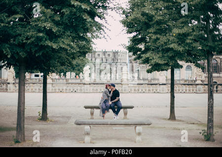 beautiful stylish young couple hugging and kissing on bench in Dresden, Germany - Stock Photo
