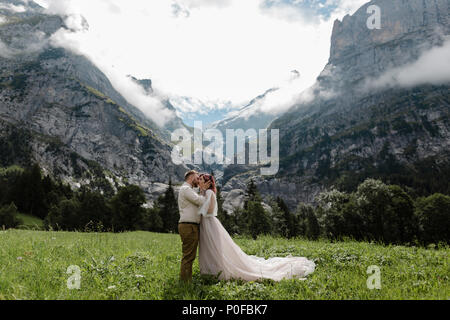 happy bride and groom hugging and kissing on green mountain meadow with clouds in Alps - Stock Photo