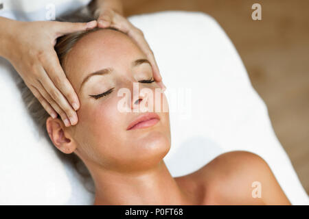 Young blond woman receiving a head massage in a spa center with eyes closed. Female patient is receiving treatment by professional therapist. - Stock Photo